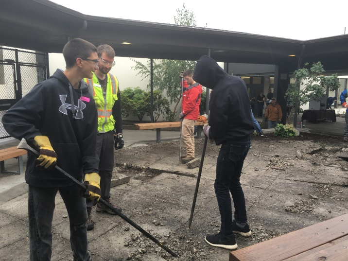 CAIS and OCHS Interact students helping break up the old concrete for an infiltration basin.